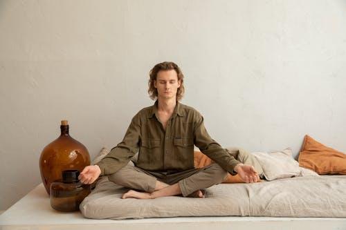 Hombre meditando en dormitorio